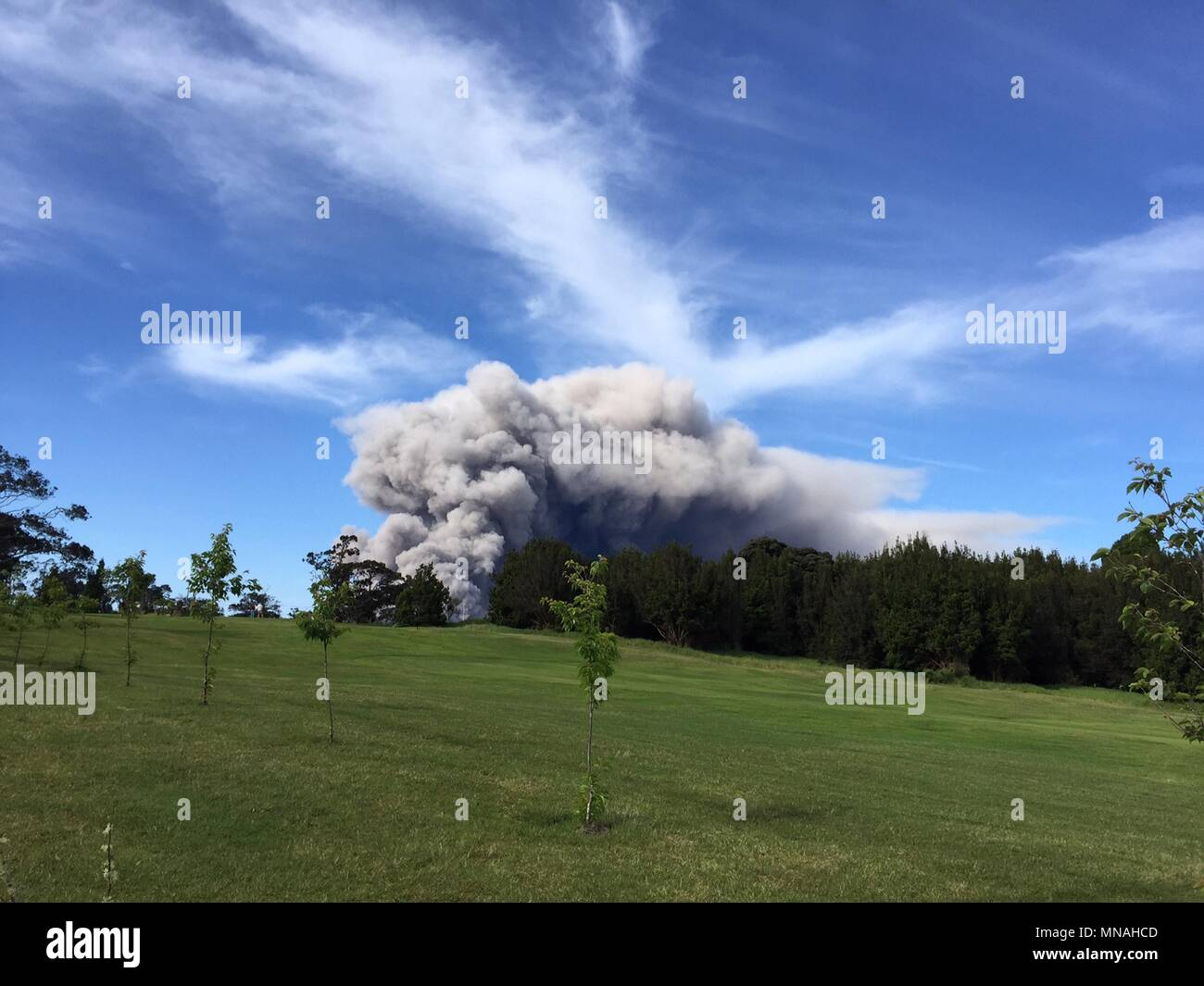 Kilauea Volcano, Hawaii. 15th may 2018. A grey ash plume rises from the Halemaumau crater in the Kilauea volcano seen from the Volcano Golf Course May 15, 2018 in Hawaii. The recent eruption continues destroying homes, forcing evacuations and spewing lava and poison gas on the Big Island of Hawaii. Credit: Planetpix/Alamy Live News Stock Photo