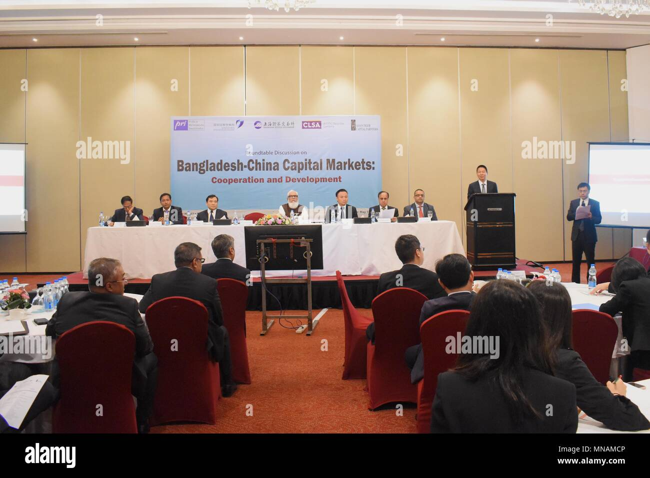 Dhaka. 16th May, 2018. Photo taken on May 15, 2018 shows the roundtable discussion on 'Bangladesh-China Capital Markets' held in Dhaka, capital of Bangladesh. The Roundtable, which has been designed to facilitate the exchange of ideas and experiences in the field of share market matters, was attended by high-level participants from the government, regulators, representatives from Bangladeshi and Chinese premier bourses, financial institutions, economic experts and journalists. Credit: Xinhua/Alamy Live News - Stock Image