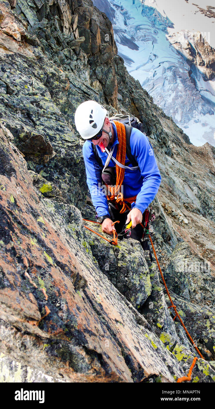 male mountain guide building a traditional belay stance with pitons to rappel from a high alpine peak - Stock Image