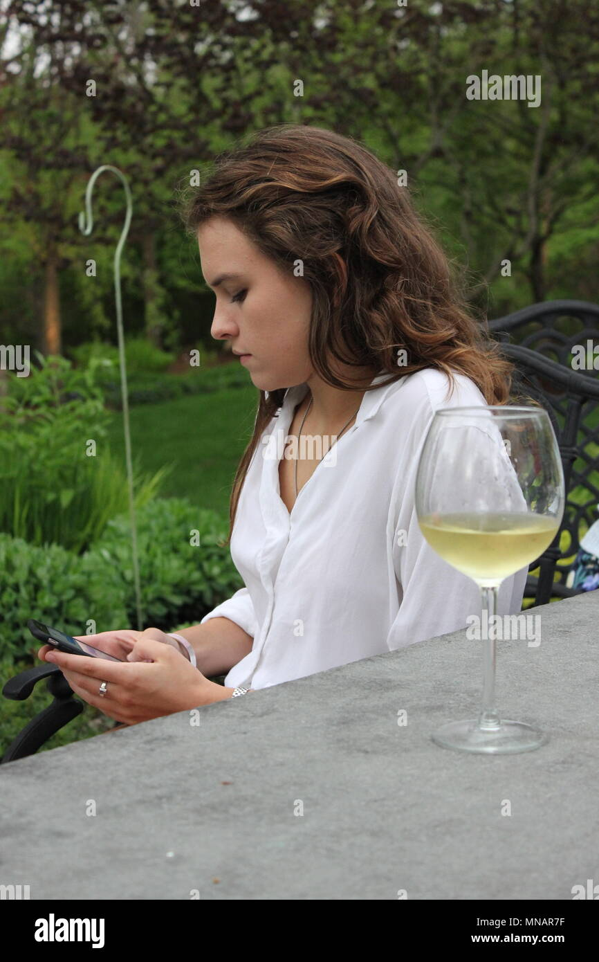 Young twenty-something woman turned away from the table and checking her phone. - Stock Image