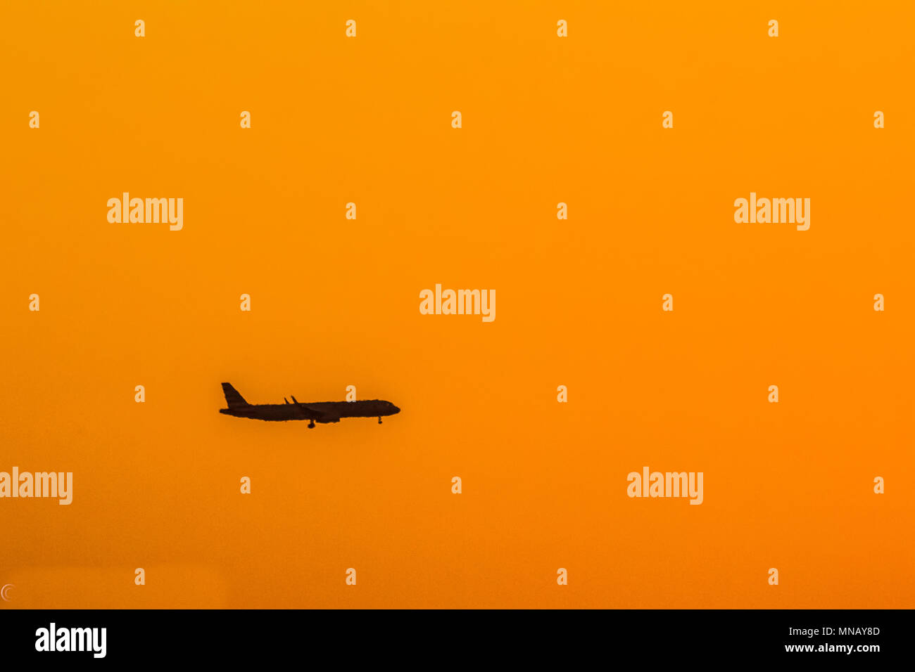 Aircraft silhouetted against bright orange morning sky - Stock Image