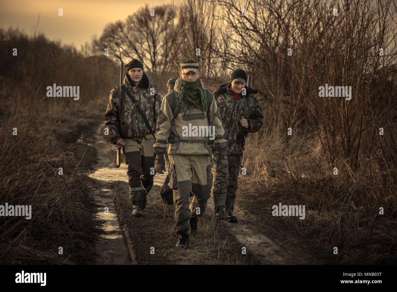 Group of men hunters with hunting equipment going on rural road hunting season sunset - Stock Image