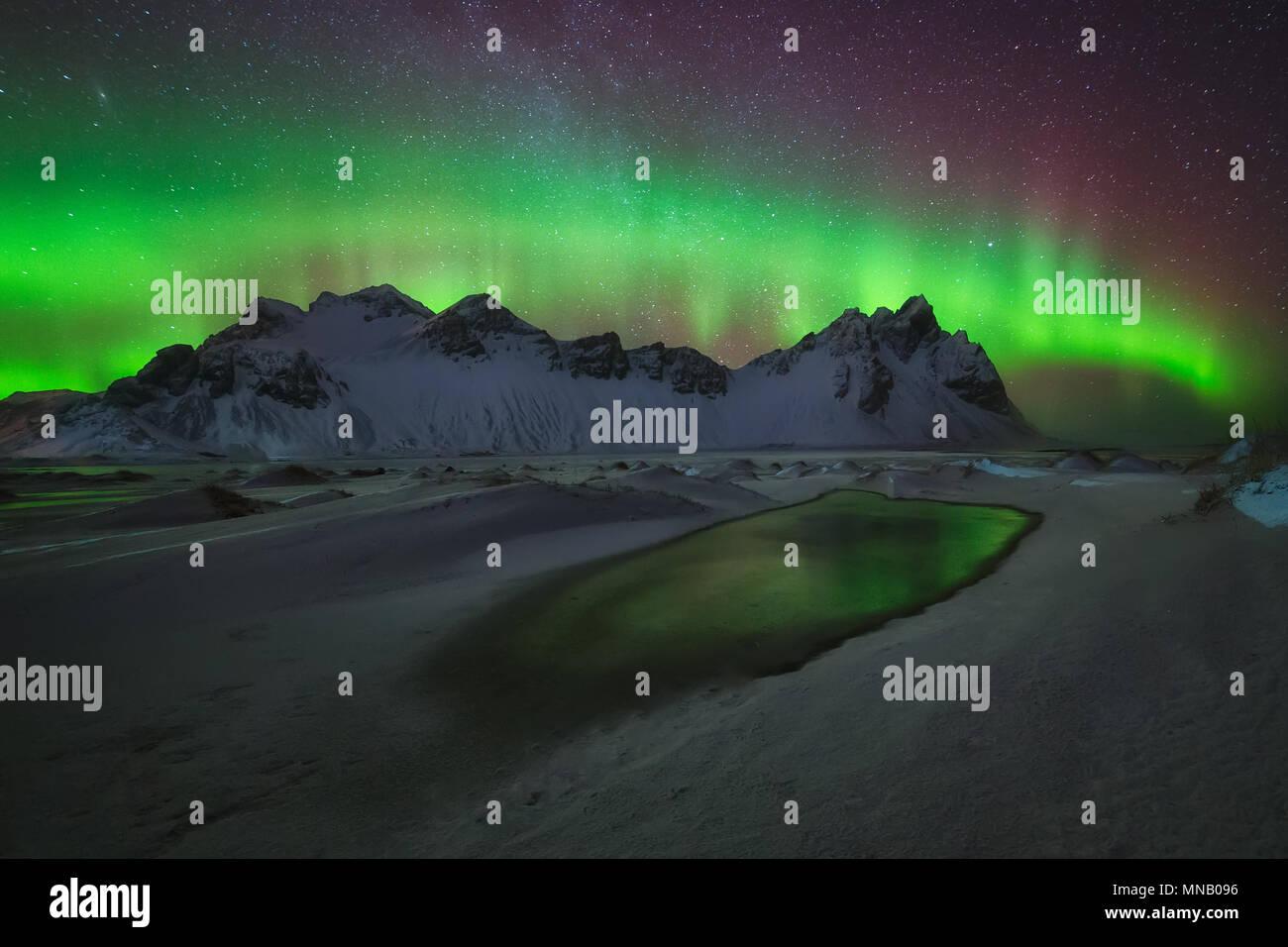Aurora Borealis green reflection over the water at Stokksnes - Stock Image