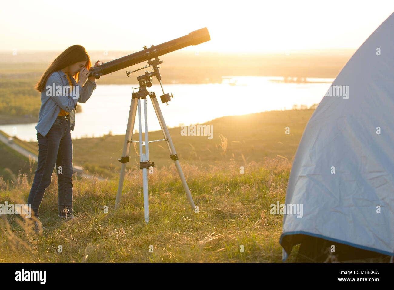 Young woman looking view through the telescope on the hill at su - Stock Image