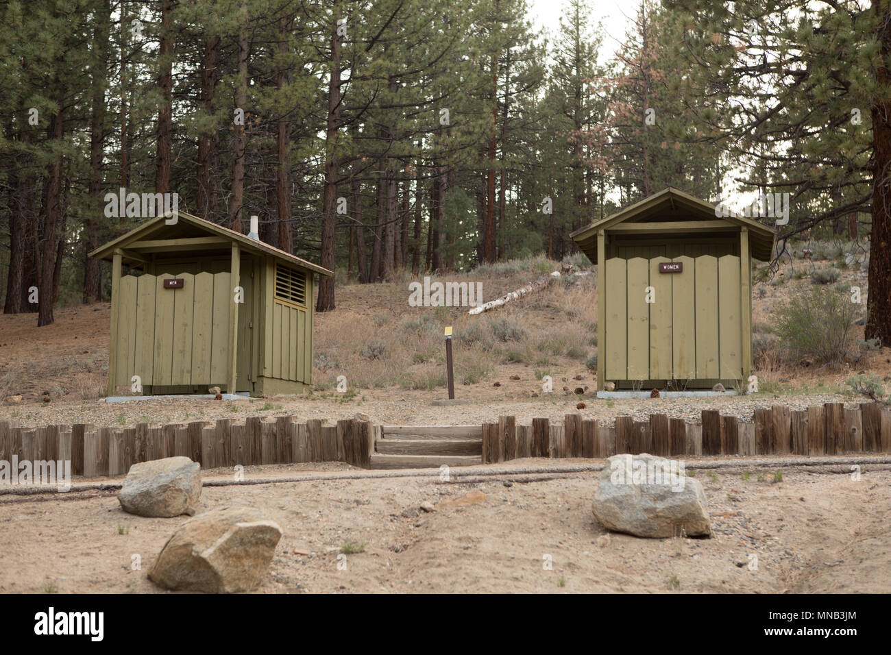 Men and women wood built campground restrooms - Stock Image