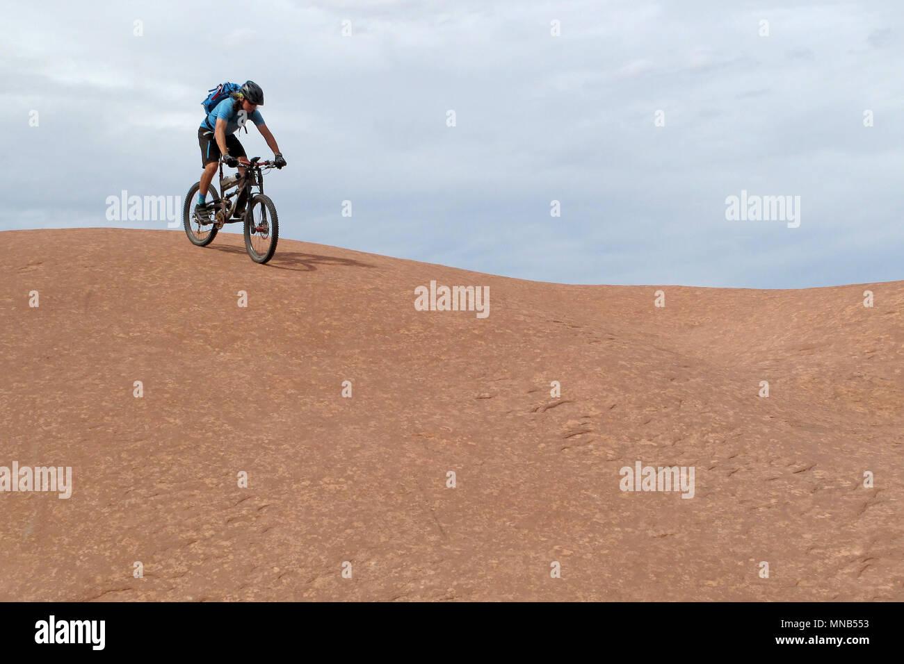 Mountain biker riding downhill the famous Slickrock trail, Moab, USA - Stock Image