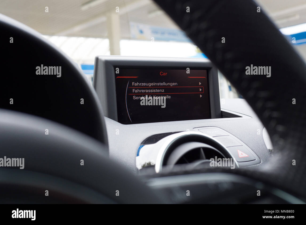 Car GPS on dashboard seen though the steering wheel. Screen on. Selective focus. - Stock Image