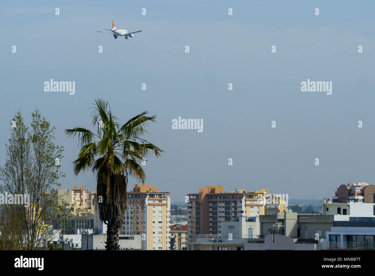 Landing plane flies at low altitude over Lisbon roofs, Portugal - Stock Image