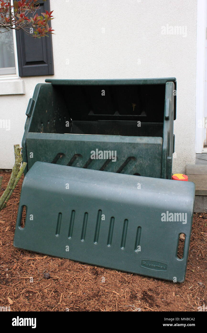 Green plastic rectangular backyard compost bin with the lid laid by the side. - Stock Image