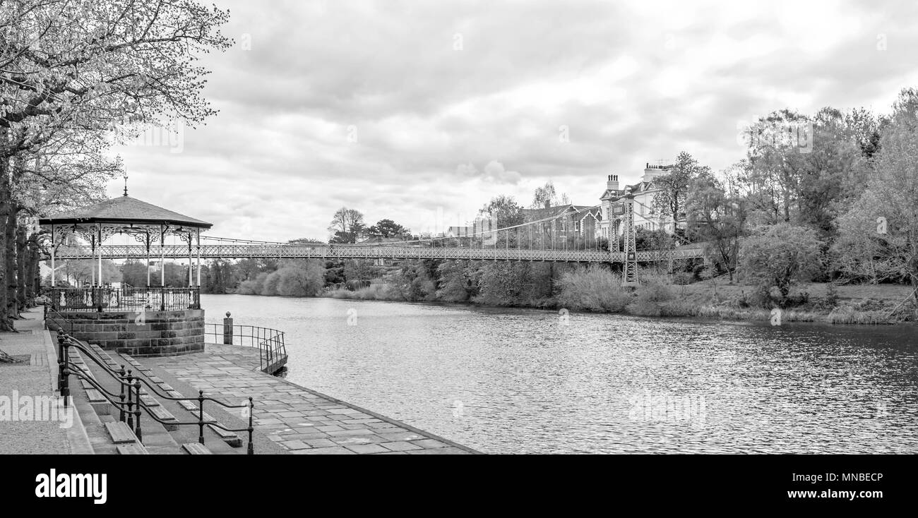 Riverbank with Victorian bandstand and view of City of Chester, Queens Park Bridge 1923, a suspension bridge across River Dee, Chester, England, UK. - Stock Image