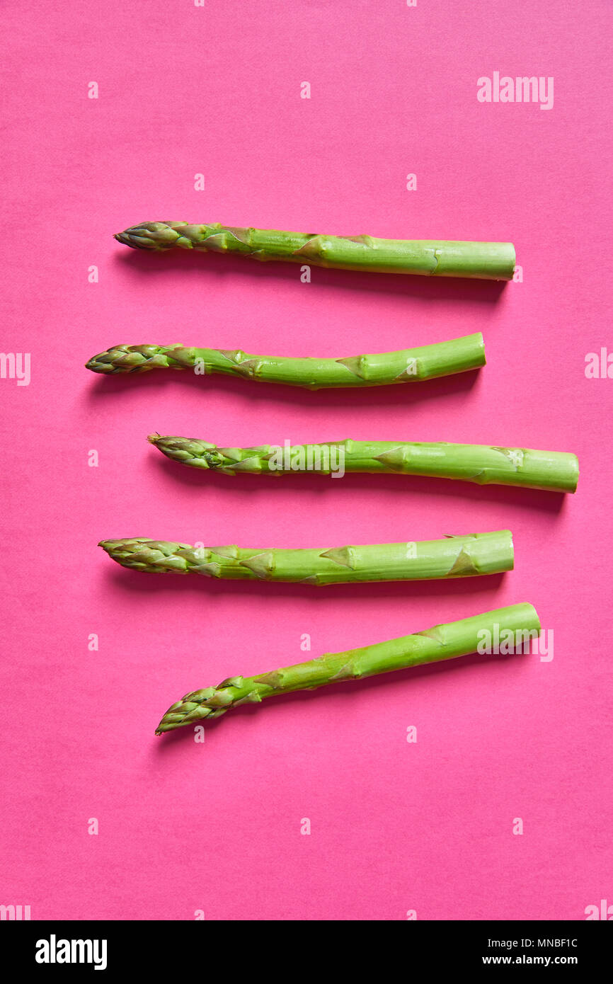 Close-up shot of five asparagus sprigs lying on pink background - Stock Image