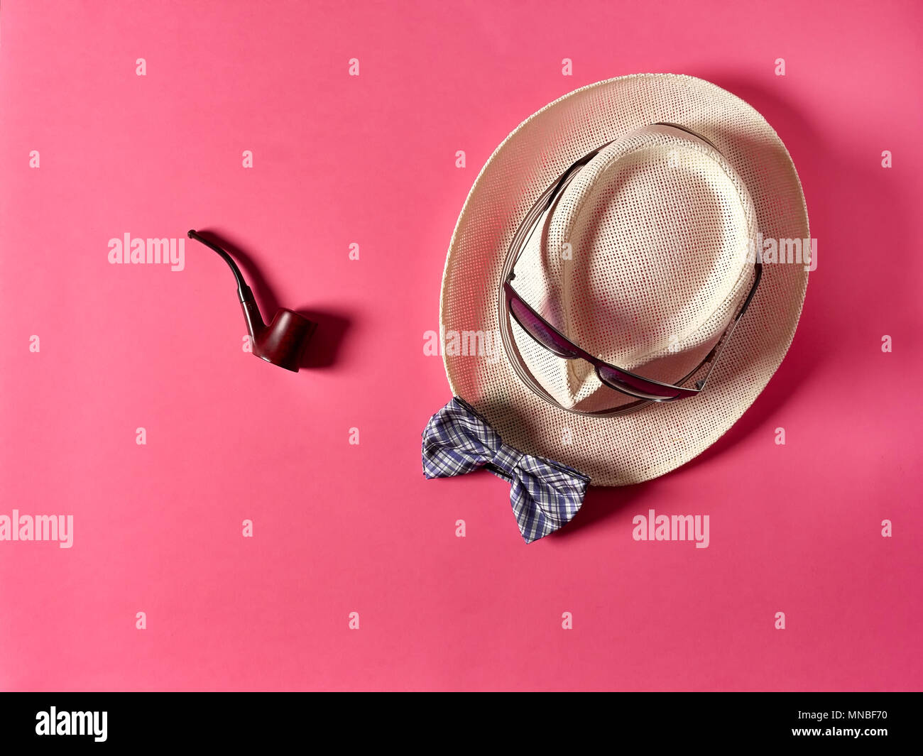 Nice smoking pipe lying on pink background near straw hat with sunglasses and bow tie - Stock Image