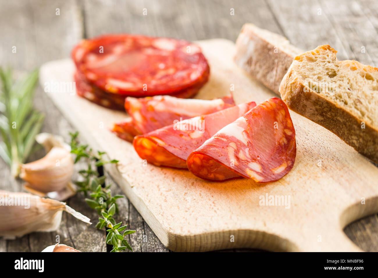 Sliced chorizo salami sausage on cutting board. - Stock Image