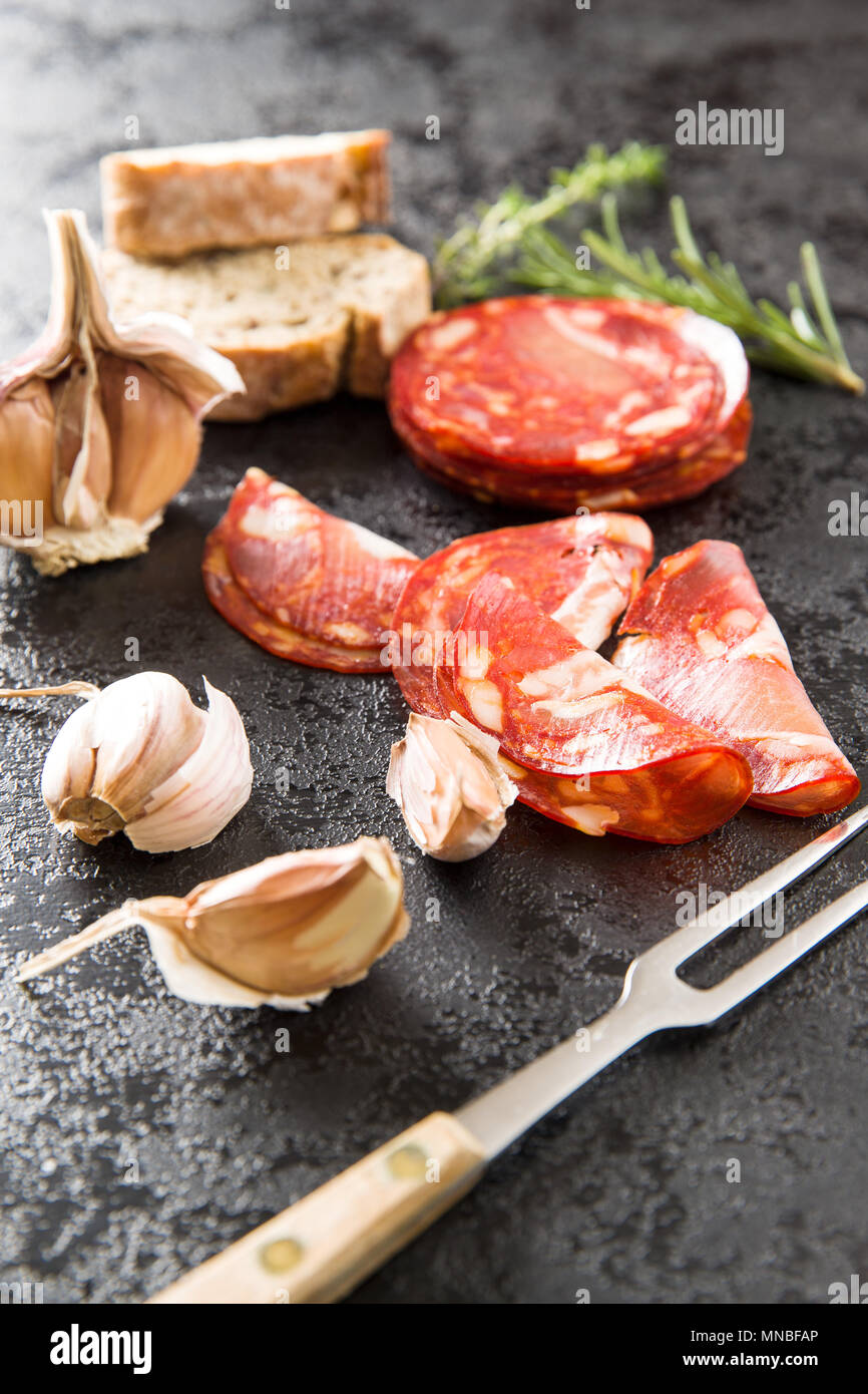 Sliced chorizo salami sausage, garlic, thyme, rosemary and ciabatta bread. - Stock Image