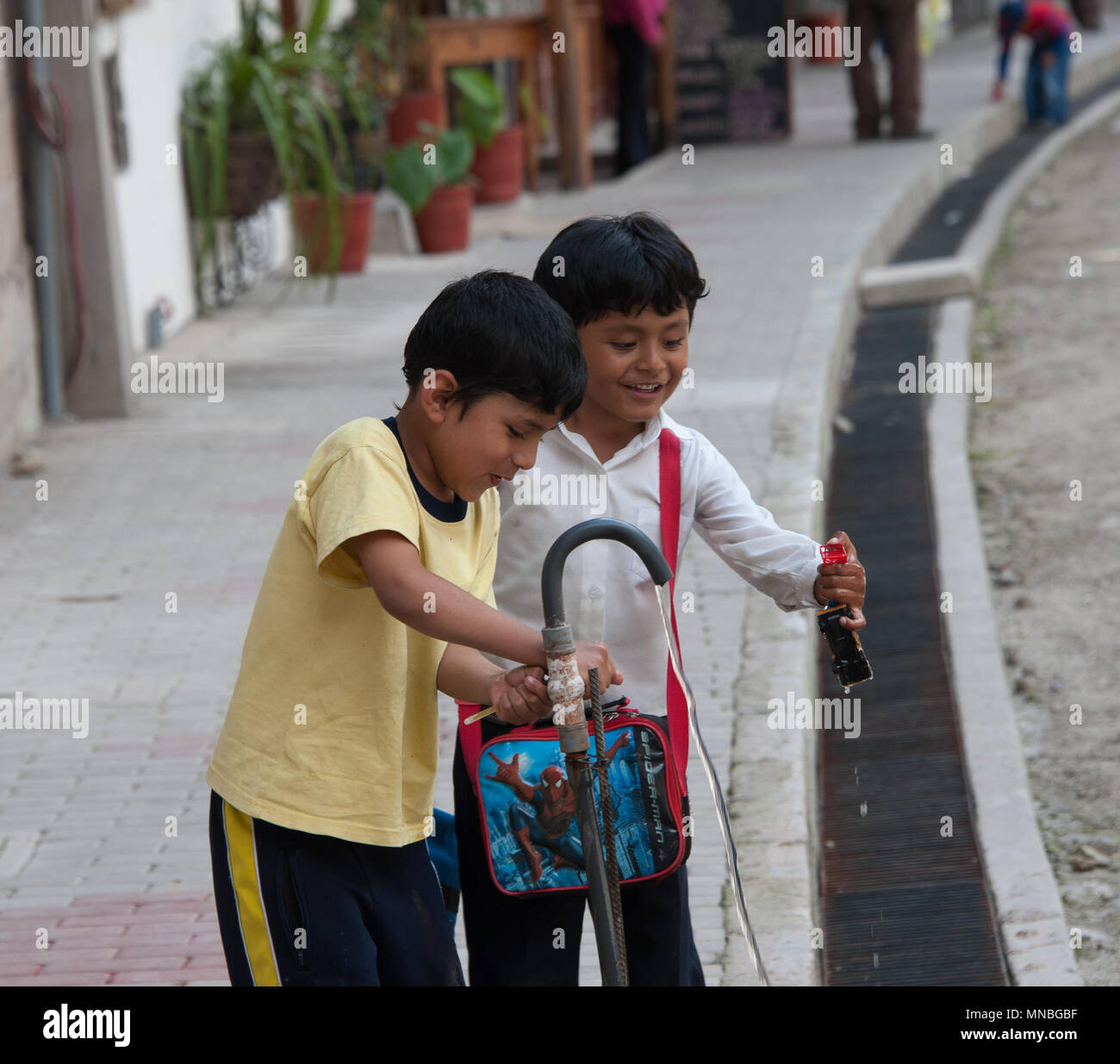 Children playing in danger near the railway track at Aguas Calientes. district of Machu Picchu. - Stock Image