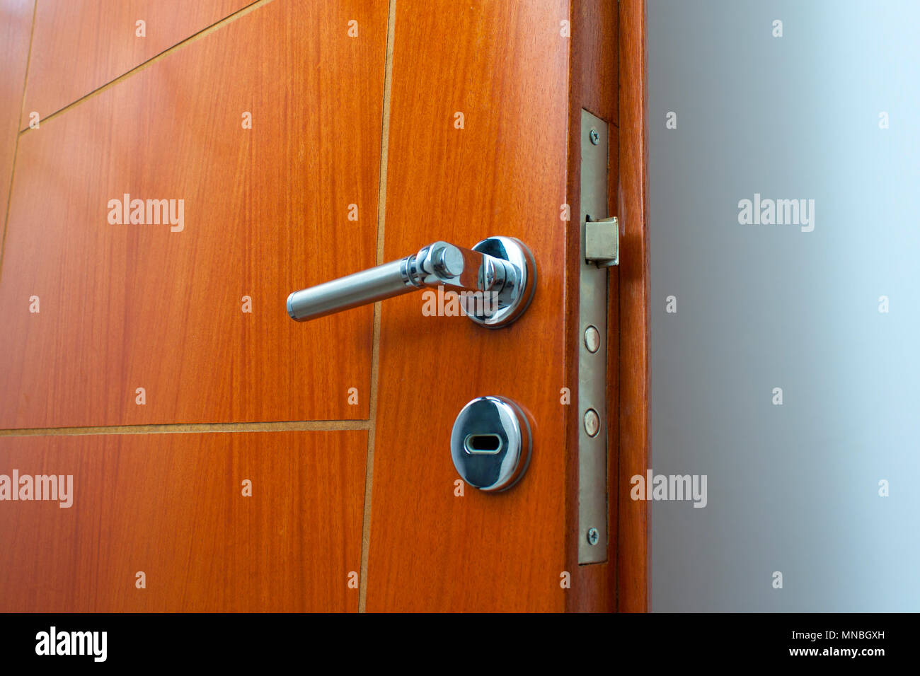 Open door of a family home. Close-up of the lock an armored door. White background. - Stock Image