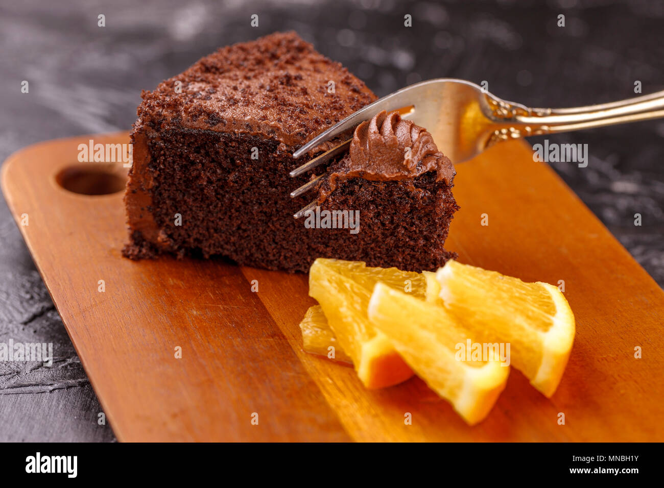 A close up image of cutting into a piece of rich chocolate cake garnished with orange slices. - Stock Image