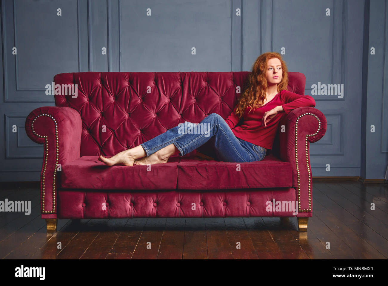 Young rich woman lying on red couch Stock Photo