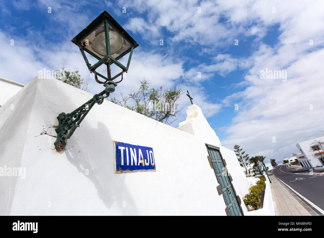 TINAJO, LANZAROTE, CANARY ISLANDS, SPAIN: Tinajo village sign and a classic lantern on a white wall with a palm tree. Stock Photo
