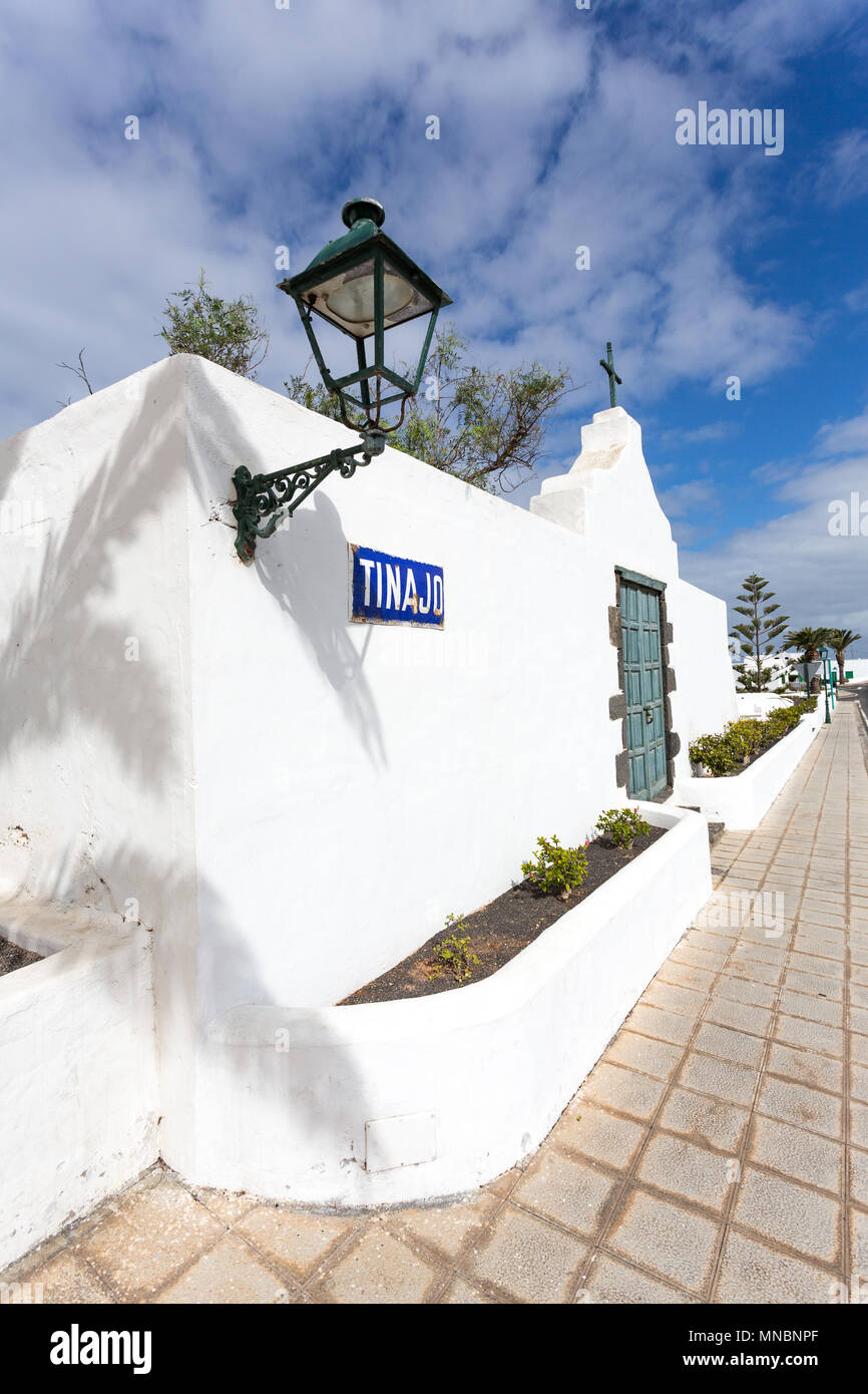 TINAJO, LANZAROTE, CANARY ISLANDS, SPAIN: Street in Tijano with a traditional white house or gate and a lantern and shadow of a palm tree. Stock Photo