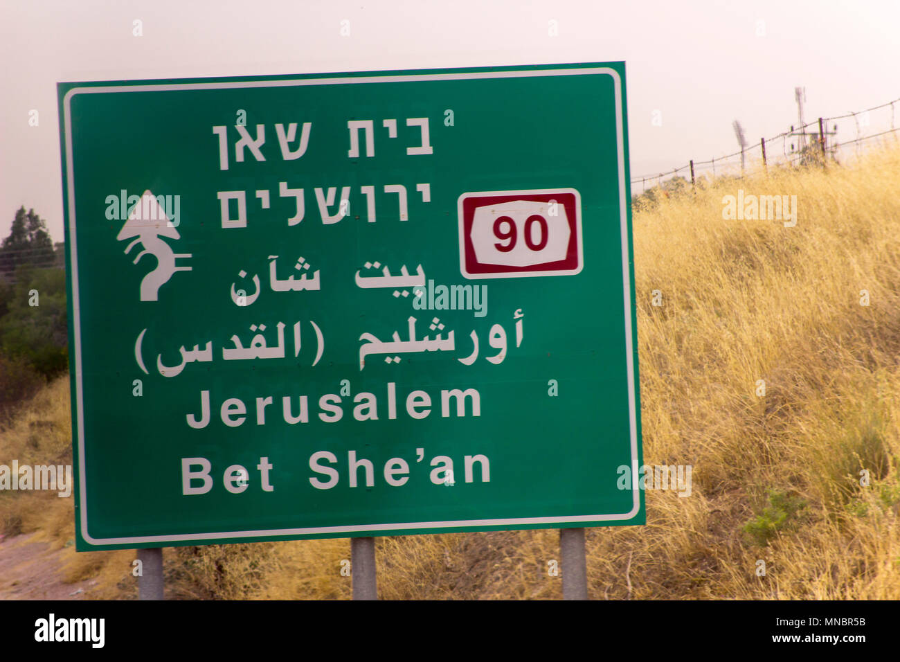 A road traffic sign for the city of Jerusalem, Israel located on the road from Qumran and taken through the window of a coach. - Stock Image