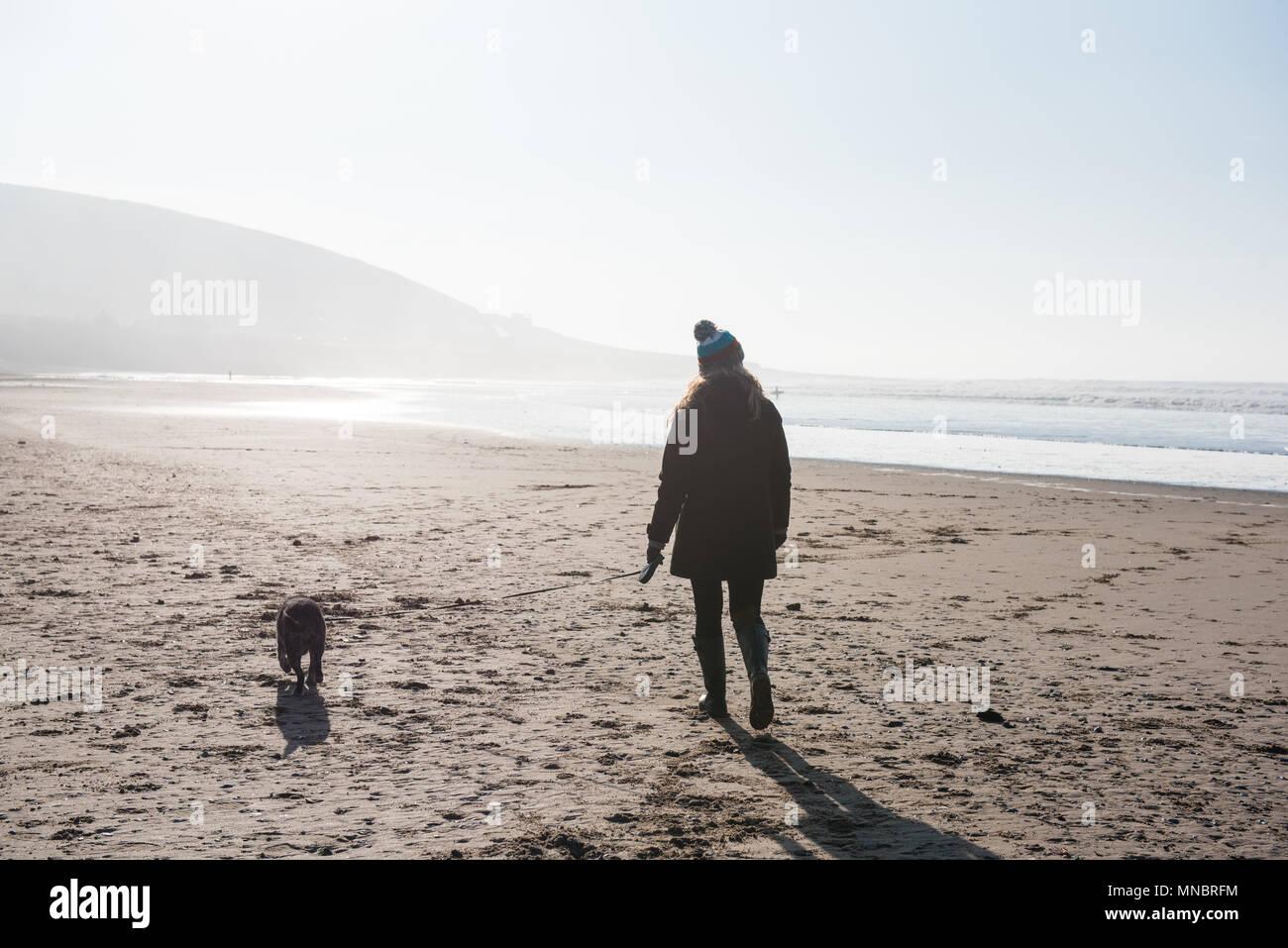 A woman walking her dog on Croyde beach Devon - Stock Image