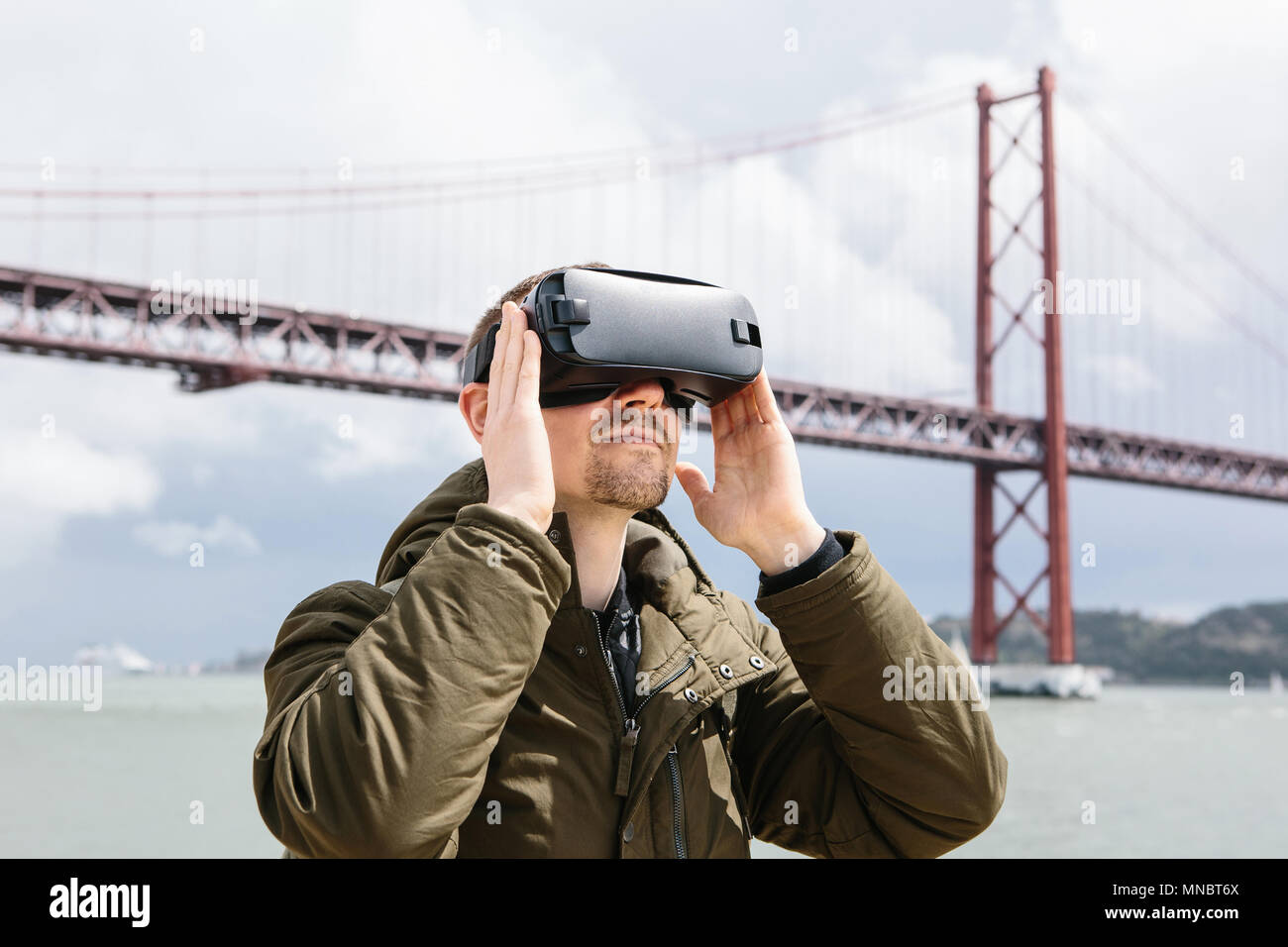 A man uses virtual reality glasses. 25th of April bridge in Lisbon in the background. The concept of virtual travel. The concept of modern technologies and their use in everyday life - Stock Image