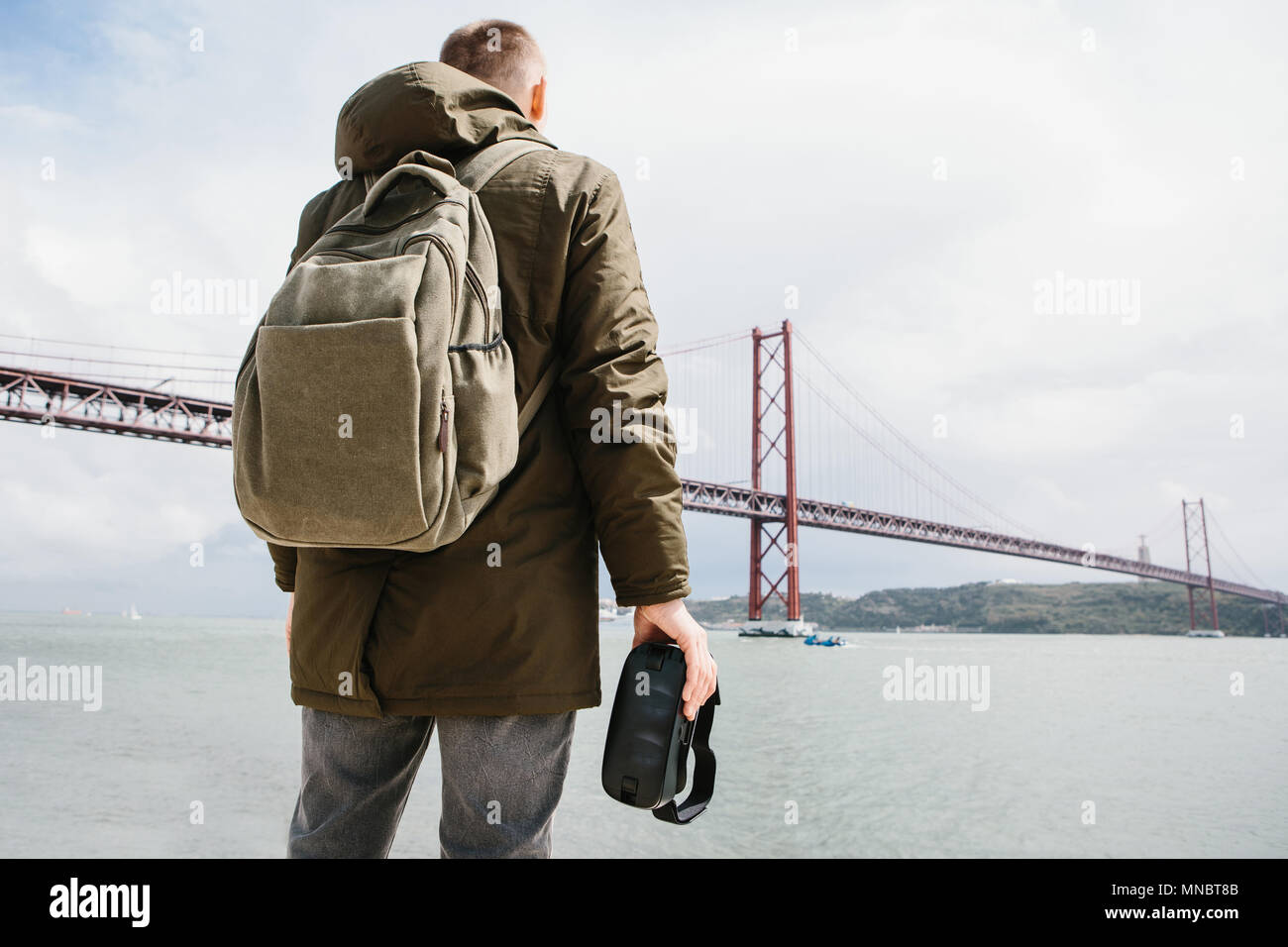The man holds the virtual reality glasses and looks at the 25th of April bridge in Lisbon. The concept of virtual travel and tourism. Modern technologies and their use in everyday life - Stock Image