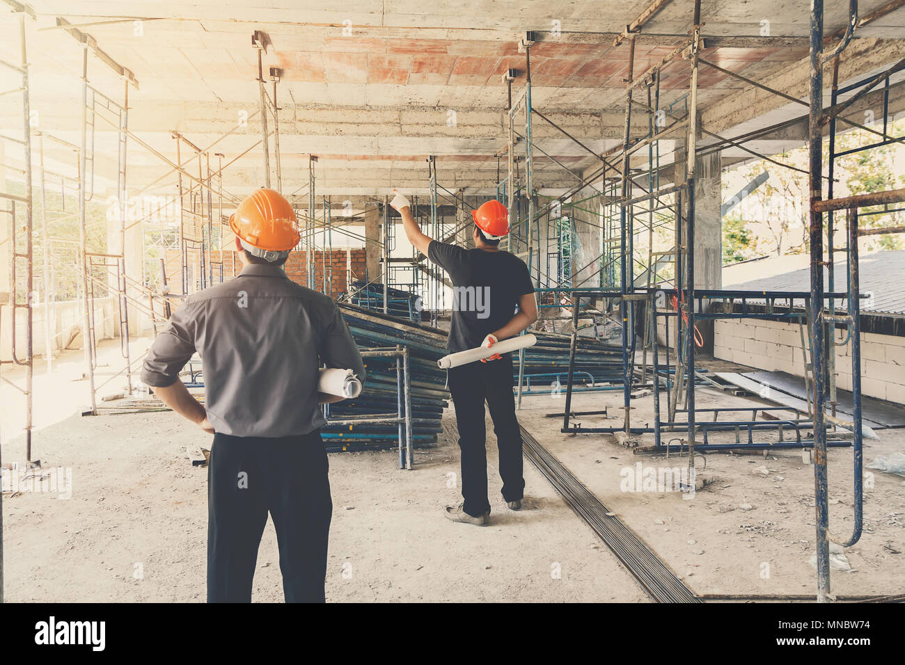 Engineer discussing with foreman about project in building construction site - Stock Image