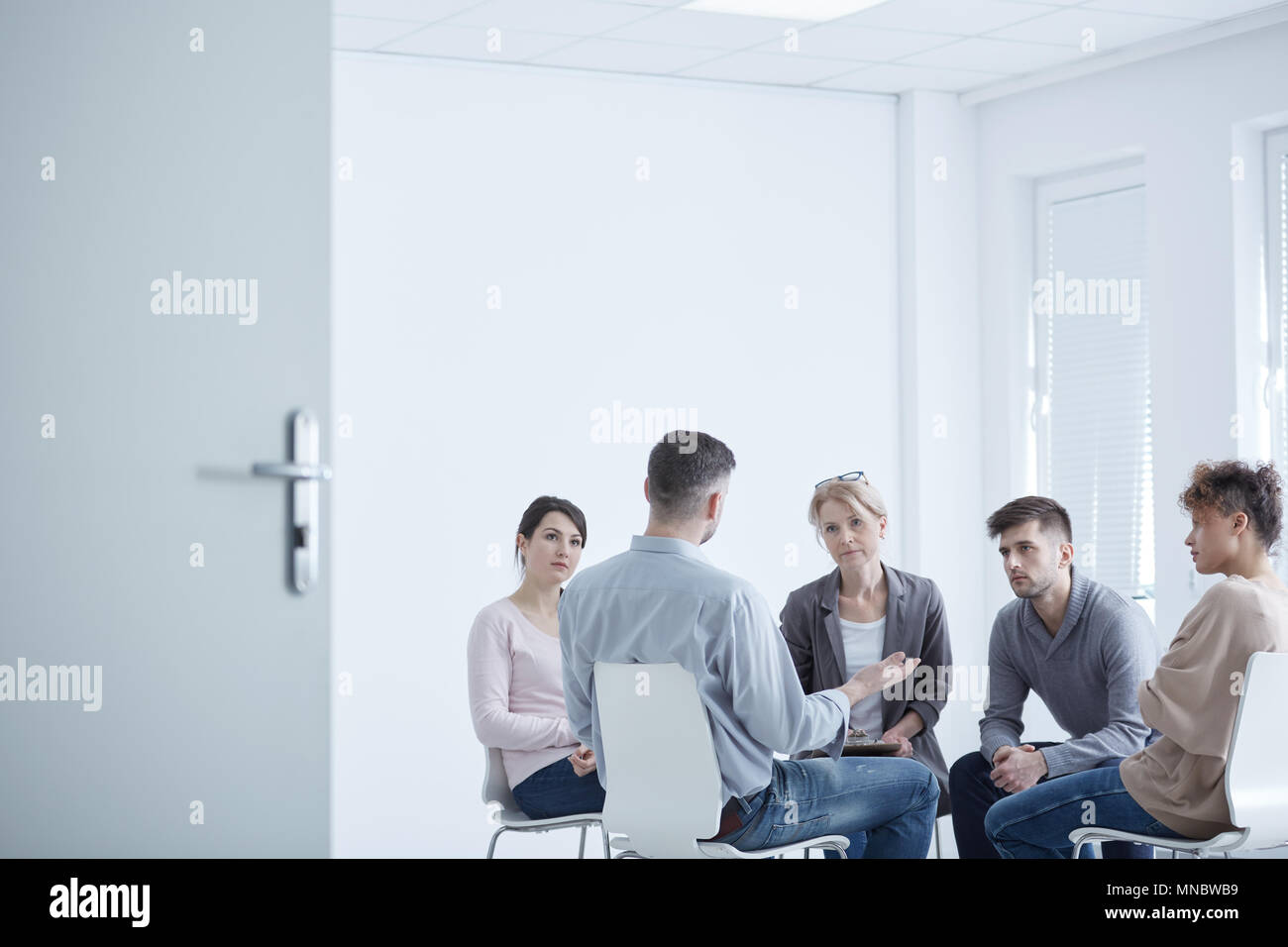People participating in group therapy for PTSD - Stock Image