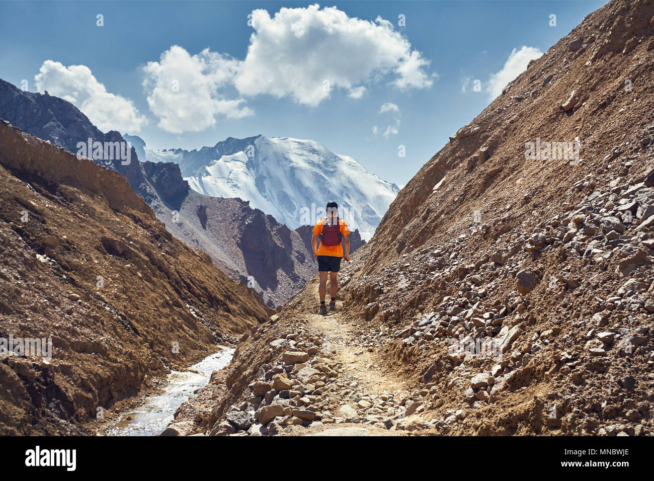 Hiker in orange shirt with backpack walking on the trail with snowy summit at background - Stock Image