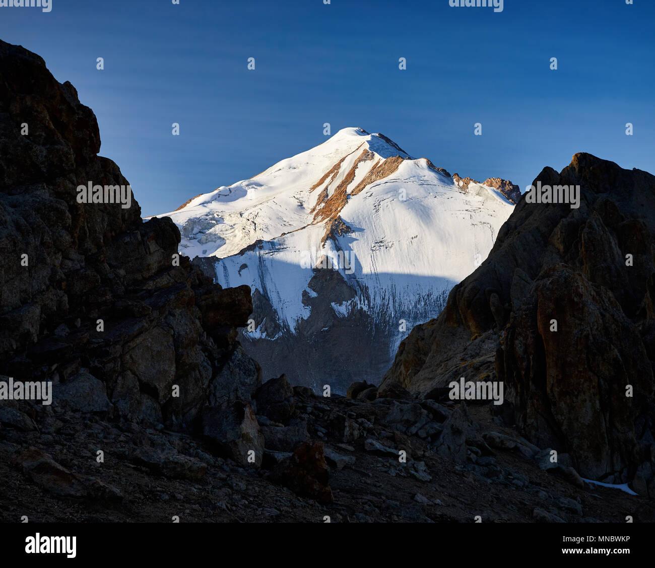 Grateful Snowy mount Sovetov between rocks silhouette at sunrise in Tyan Shan mountain range in Kazakhstan - Stock Image