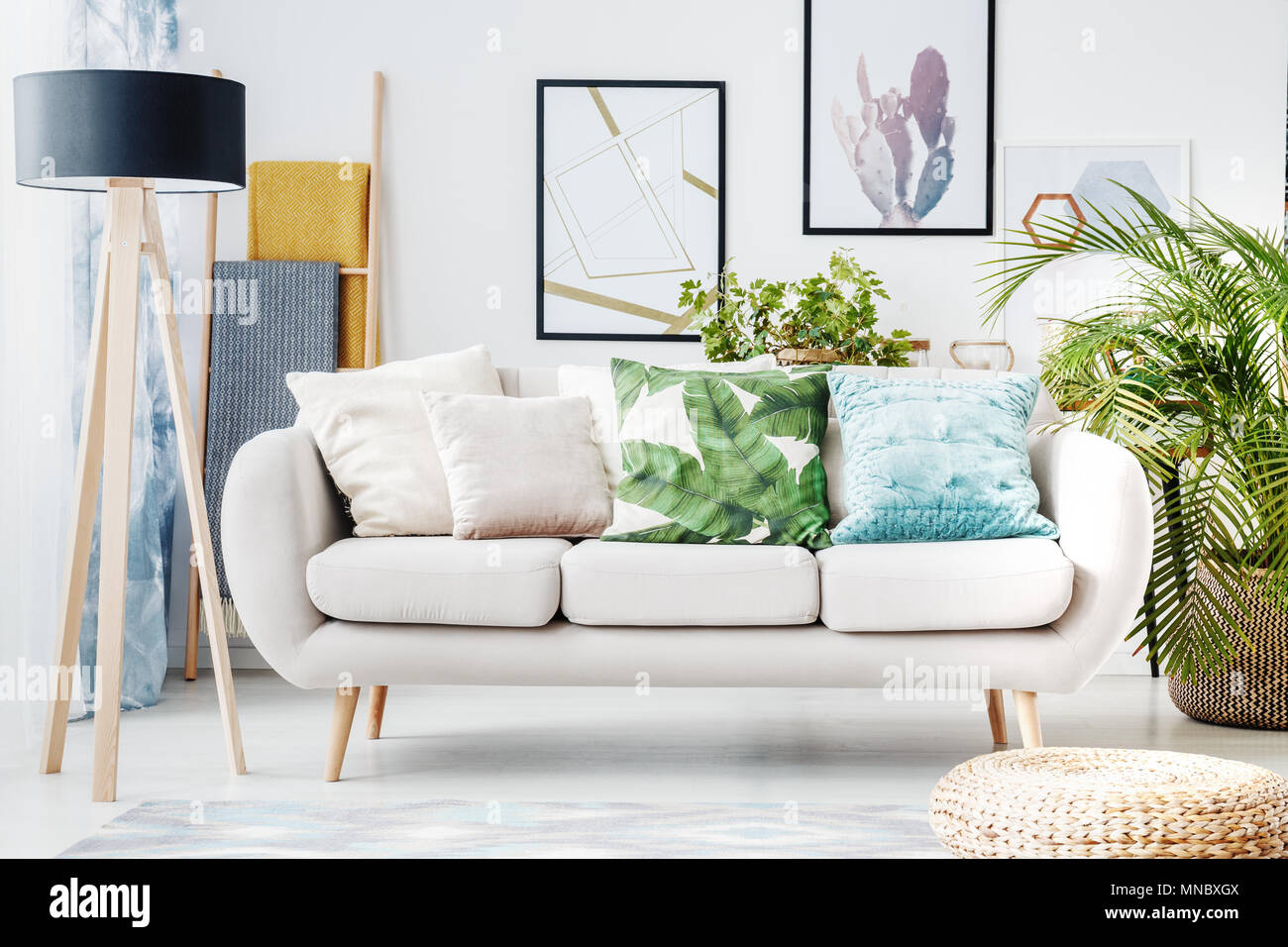 Floral cushion on a beige sofa and posters on the wall in living ...