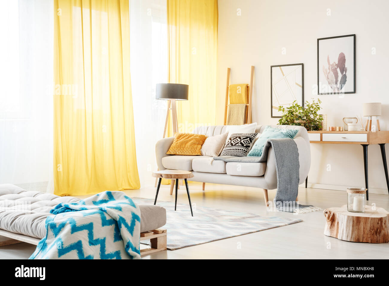 Patterned Blanket On Settee And Candle On Wooden Stump In Spacious Living  Room With Yellow Curtains And Beige Sofa