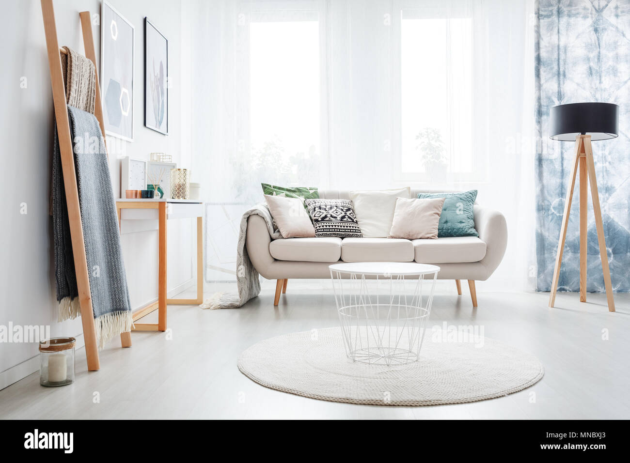 White round carpet in bright living room with lamp and ladder near ...