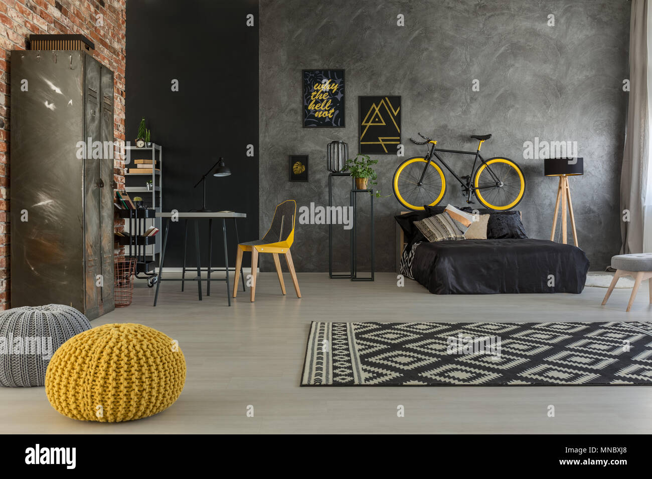 Grey apartment with bed, desk, chair, brick wall, yellow details - Stock Image