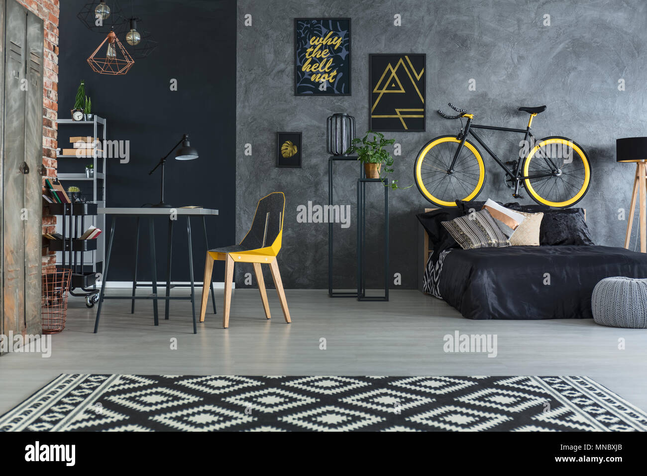 Hipster bedroom with bed, desk, chair and brick wall - Stock Image