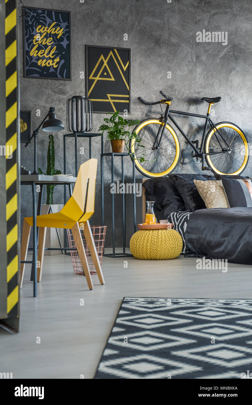 Functional grey bedroom with bed, chair and desk - Stock Image