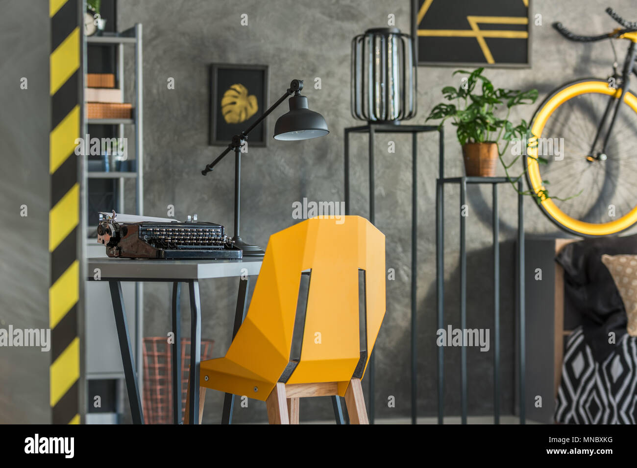 Grey home office with old typewriter and yellow chair - Stock Image
