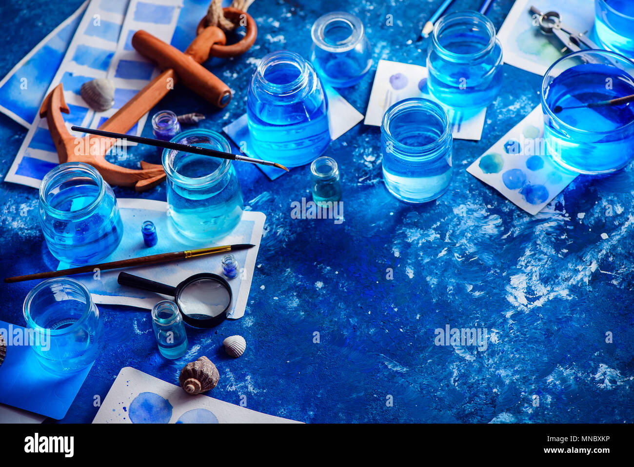 Creative artist workplace with marine watercolor, palettes, swatches, brushes and water jars from above. Painting sea concept on a navy blue backgroun Stock Photo