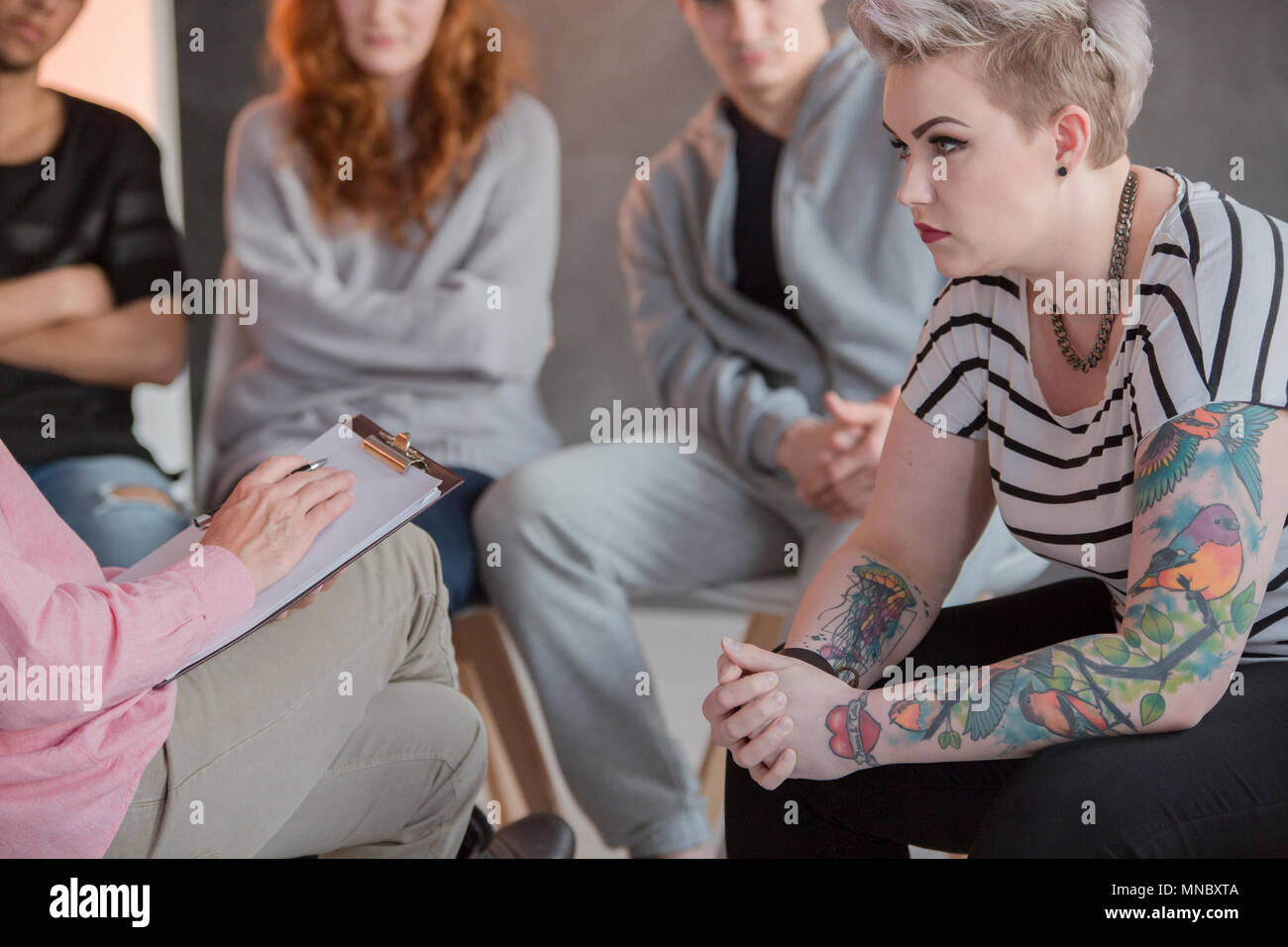 Rebellious girl with emotional problems during group psychotherapy Stock Photo