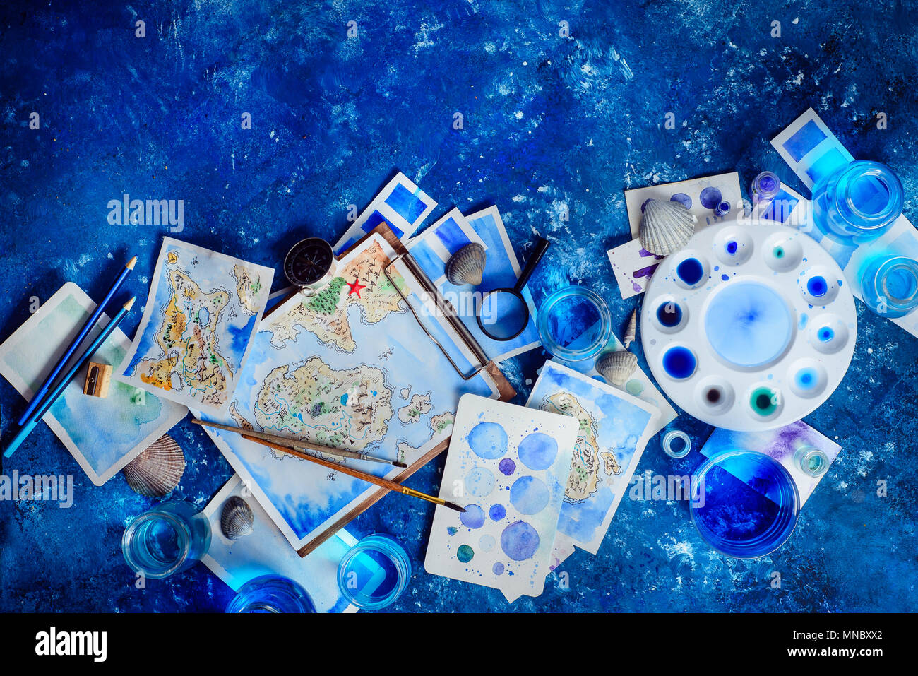 Artist workplace with a watercolor map, sketches, seashells and compass on a navy blue background with copy space. Travel flat lay header. - Stock Image
