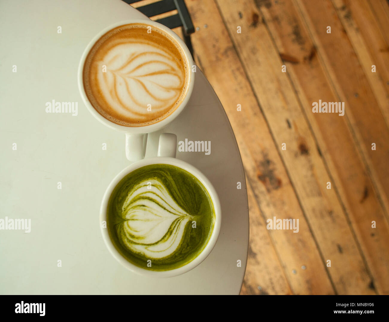 Two cups of matcha tea and cappuccino with beautiful latte art on grey color table. - Stock Image
