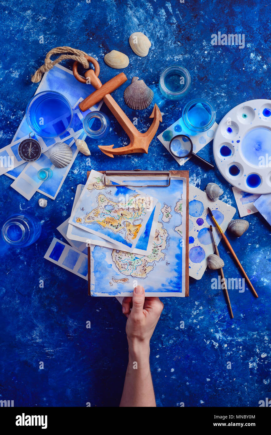 Hands holding a hand-painted map on a clipboard. Marine watercolor concept. Creative artist workplace flat lay. - Stock Image
