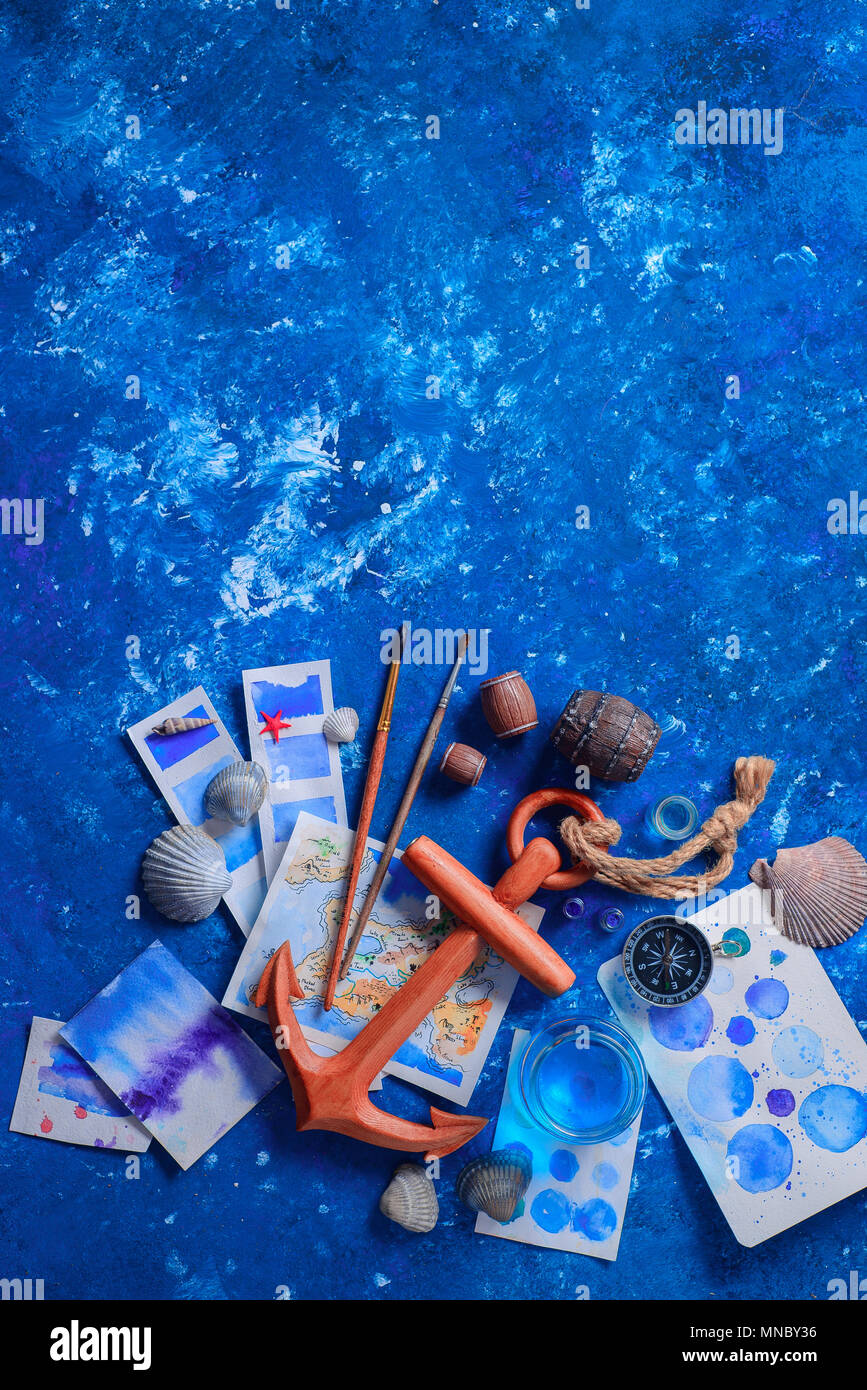 Travel flat lay with wooden anchor, fantasy map, watercolor sketches, seashells and compass on a navy blue background with copy space. Creative artist - Stock Image