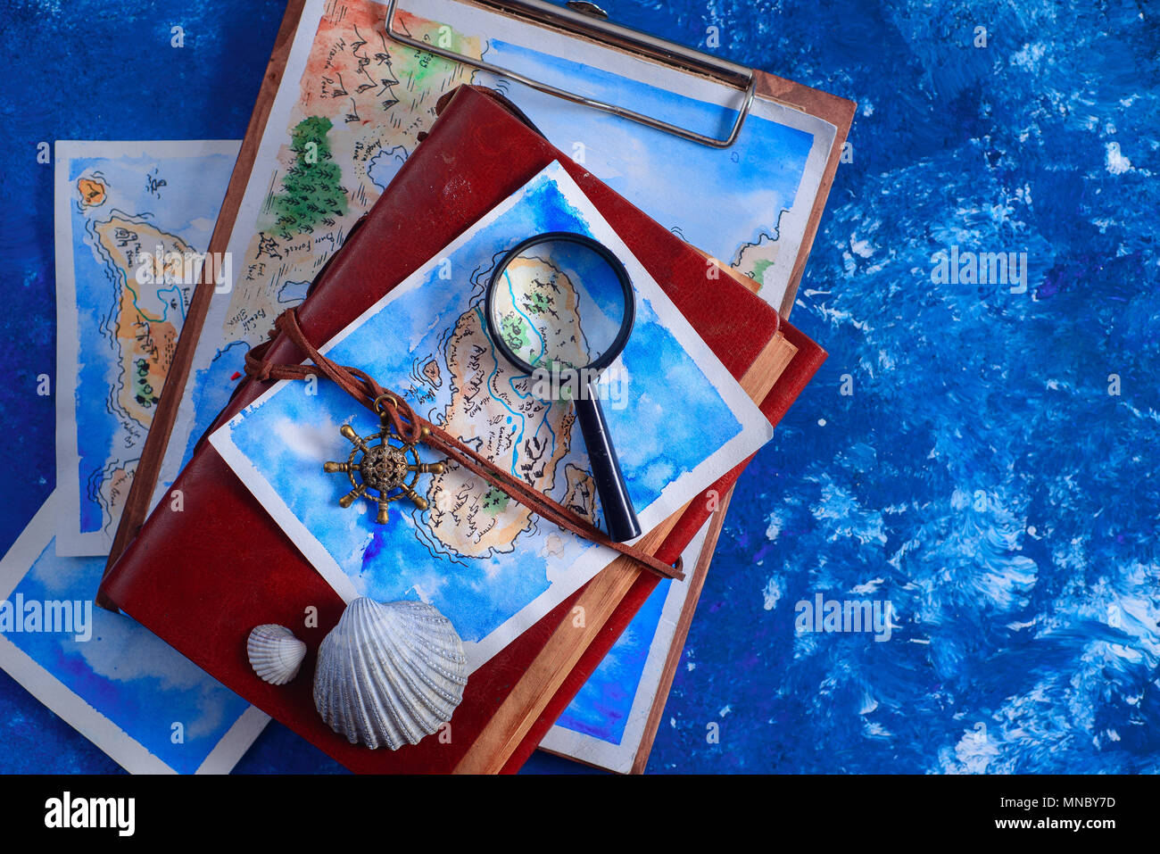 Sea travel and painting concept. Watercolor fantasy map on leather cover captain journals with a magnifying glass on a navy blue background with copy  Stock Photo