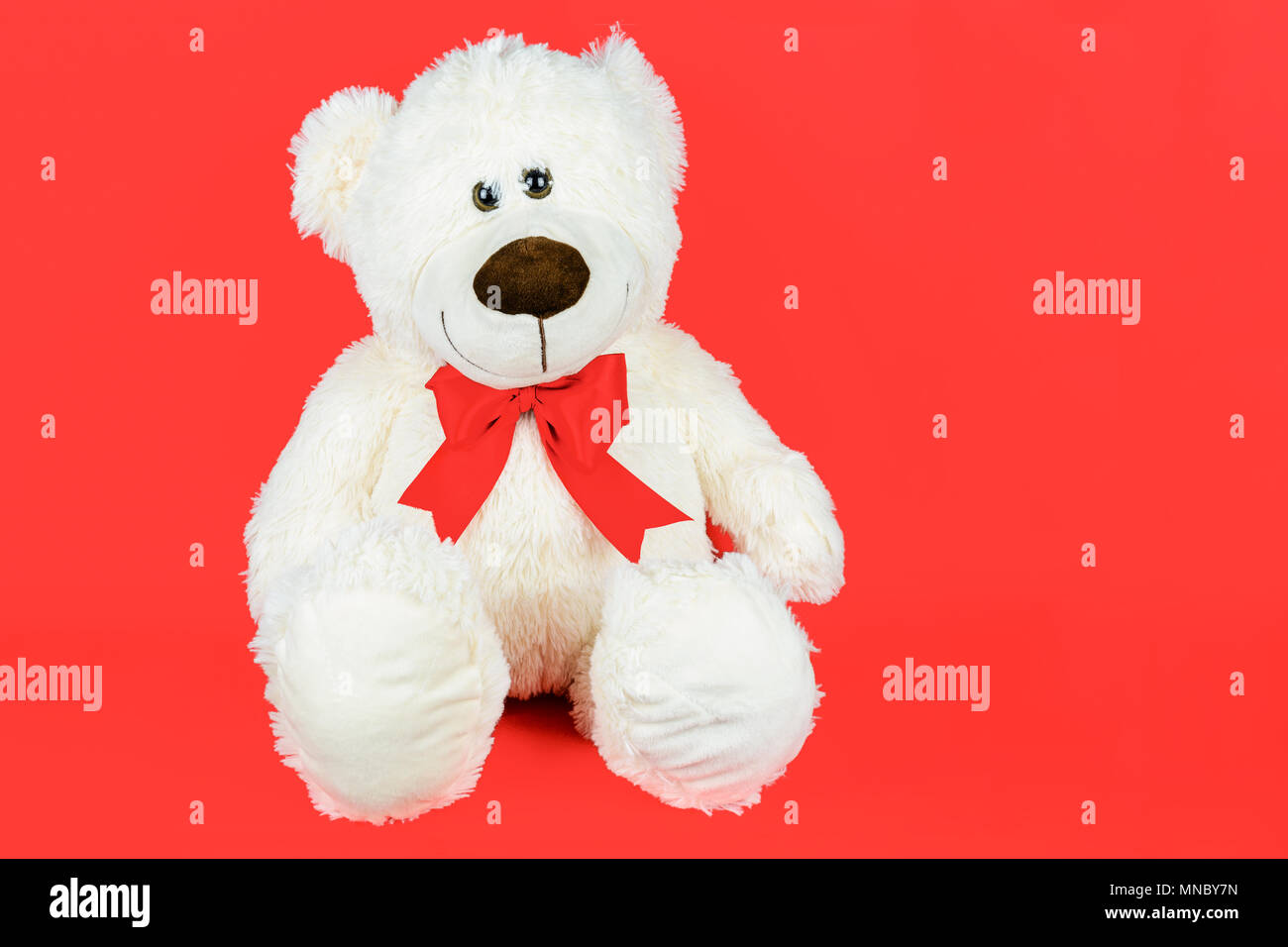 Greetings card concept - white teddy bear with a bow isolated on a red background (copy space) - Stock Image