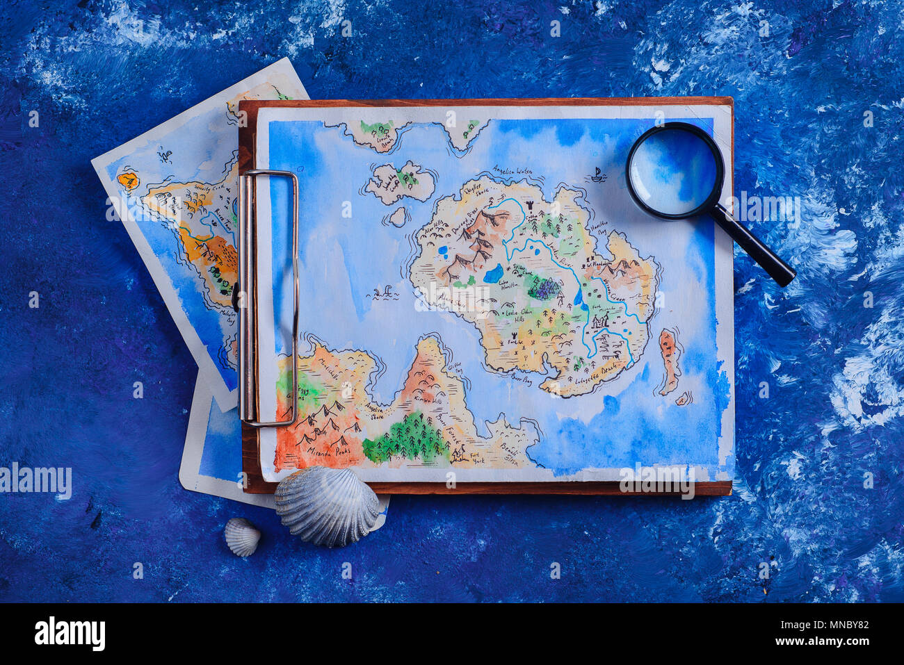 Sea travel and painting concept. Watercolor fantasy map on a wooden clipboard with a magnifying glass on a navy blue background with copy space. Stock Photo
