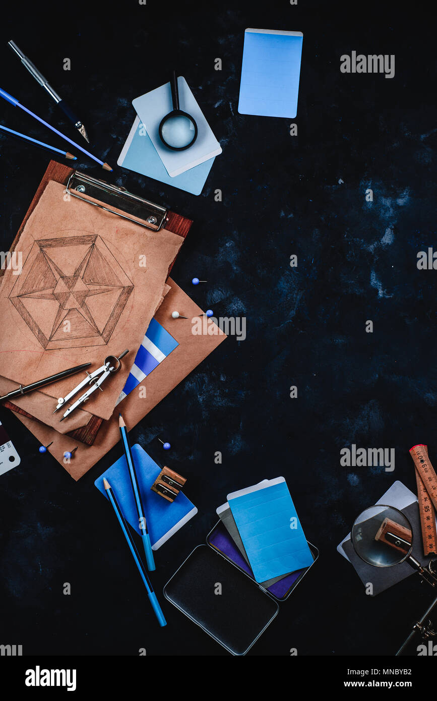 Architect or interior designer workplace, desk and design tools with construction material samples. Sketches, compasses, rulers, clipboards and pencil - Stock Image