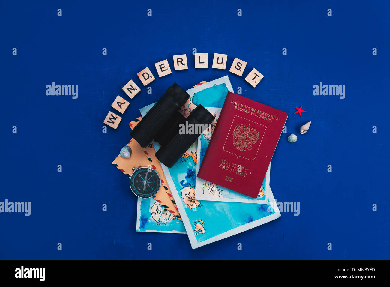 Travel and exploration concept with watercolor maps, passport, compass, binoculars, envelopes, magnifying glass, and Wanderlust scrabble letters. Vaca - Stock Image